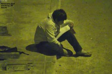 Niño utiliza luz del poste para realizar sus tareas escolares
