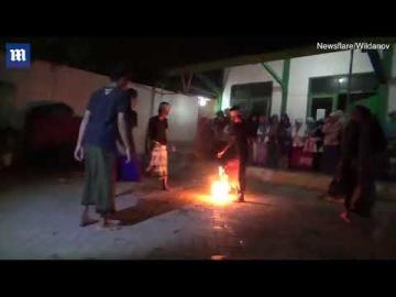 Schoolchildren play dangerous game of 'fire football' barefoot